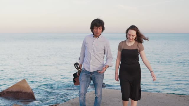 Beautiful musician couple walk walk along the pier by the sea video