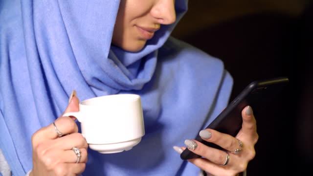 beautiful muslim girl using smartphone in cafe. modern muslim woman and new technologies - abbigliamento religioso video stock e b–roll