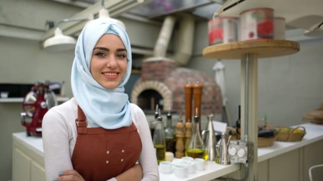 beautiful muslim woman business owner of a restaurant looking at camera smiling with arms crossed - etnia medio orientale video stock e b–roll