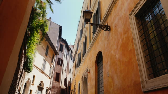 Beautiful narrow street in the old part of Rome, Italy. Medieval buildings covered with ivy. Steadicam shot video