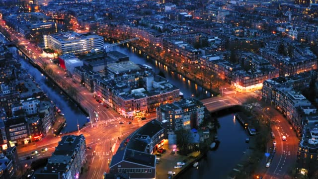 Beautiful night aerial view of Amsterdam downtown from above with many narrow canals, illuminated streets and old historic houses, drone footage