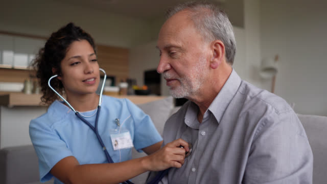 vídeos de stock e filmes b-roll de beautiful nurse checking a senior patient for the stethoscope at home - exame
