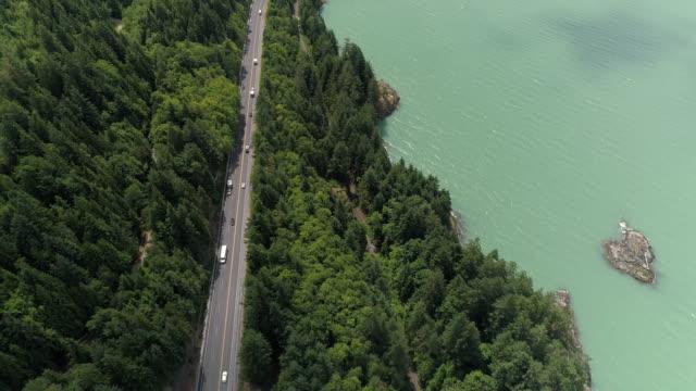 schöne meer autobahn antenne des menschen auf roadtrip durch grünwald und türkisblaues wasser - vancouver kanada stock-videos und b-roll-filmmaterial