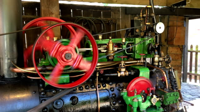 Beautiful old steam engine machine working with large leather belt and fast moving pistons