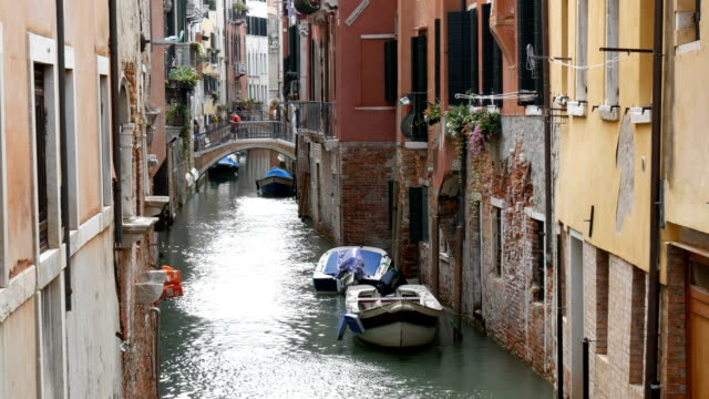 Beautiful old walls of vintage houses on Venetian canal, people stroll through the old concrete bridge over the canal video