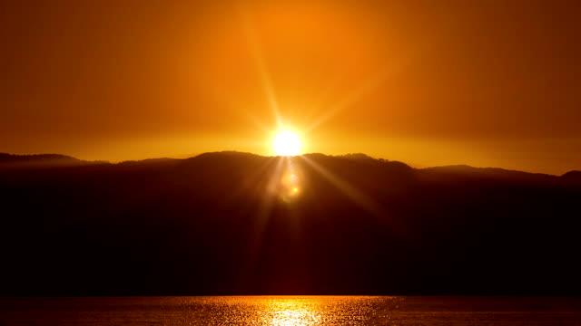 vídeos de stock, filmes e b-roll de laranja belo nascer do sol sobre o mar. hd 1080. - acima