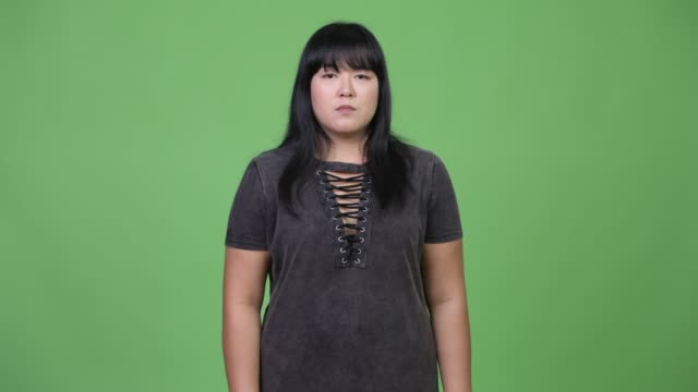 Beautiful overweight Asian woman covering ears as three wise monkeys concept Studio shot of beautiful overweight Asian woman against chroma key with green background one mid adult woman only stock videos & royalty-free footage