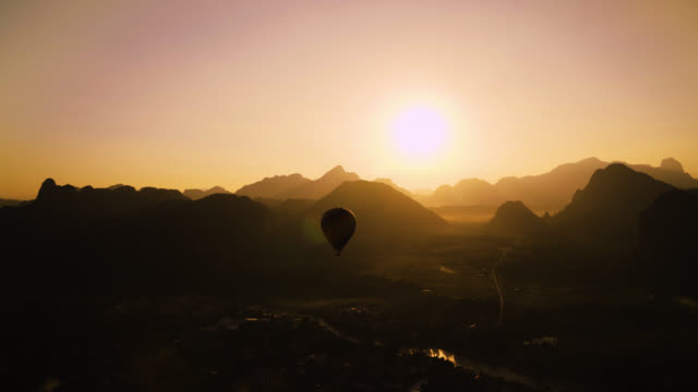 beautiful panoramic nature landscape of countryside mountains in vang vieng, laos. the cloudless sunset in the distance while a hot air balloon floats along - vivid 4k video stock videos & royalty-free footage