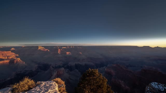 Beautiful panoramic panning timelapse looking over the Grand Canyon south rim as the sun rises over the horizon bringing light onto the snow covered red rock cliffs.