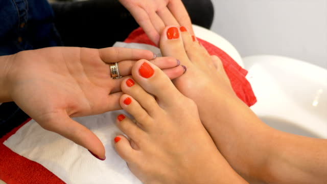 Beautiful pedicure with red nail polish presented for evaluation at nail art technician course video