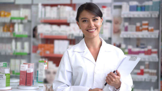 Beautiful pharmacist at a drugstore looking at the camera smiling video
