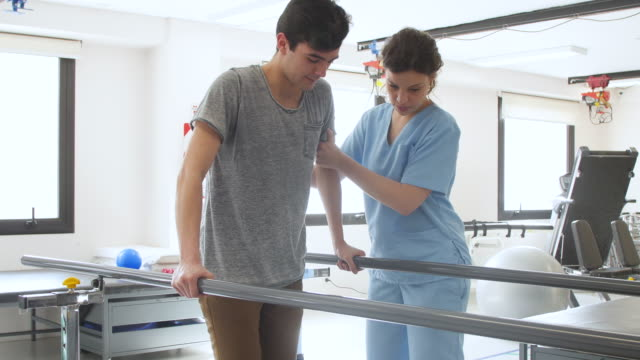 beautiful physical therapist helping male patient walk while leaning on parallel bars both looking happy - fisioterapia video stock e b–roll