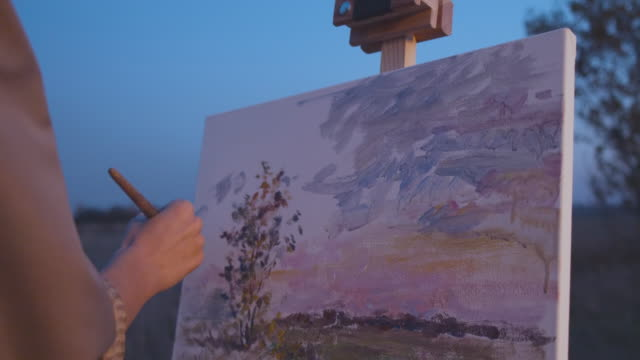Beautiful piece of art on easel, artist making final stroke with brush on canvas