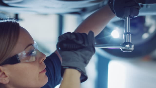 Beautiful Portrait of a Professional Female Car Mechanic is Working Under a Vehicle on a Lift in Service. She is Using a Ratchet. Specialist is Wearing Safety Glasses. Modern Clean Workshop.