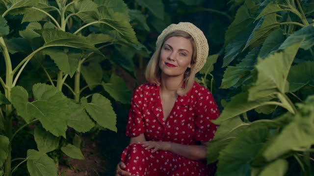 vídeos de stock e filmes b-roll de beautiful portrait of attractive blonde woman in straw beret hat . girl sitting between plants.nature background. retro floral dress, red lips. pleasant feminine appearance, kind smile. 4k slow motion - só mulheres jovens