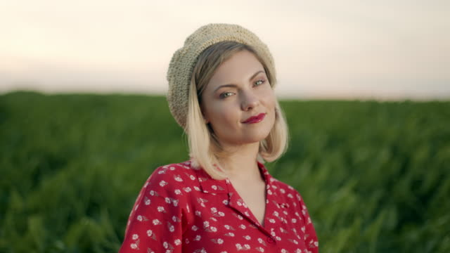 vídeos de stock e filmes b-roll de beautiful portrait of attractive blonde woman in straw beret hat on green nature background. retro floral dress, red lips. pleasant feminine appearance, kind smile. 4k slow motion - só mulheres jovens