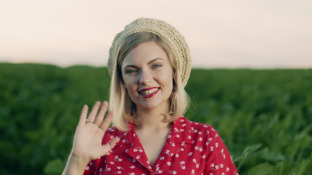vídeos de stock e filmes b-roll de beautiful portrait of attractive blonde woman waving hand, smiling, greeting. lady in straw beret hat on green nature background. pleasant feminine appearance, kind smile. 4k slow motion - só mulheres jovens