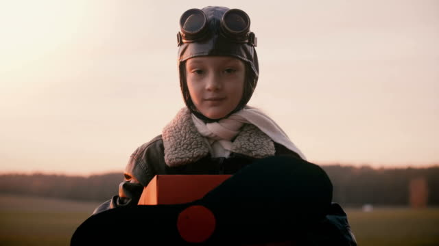 Beautiful portrait shot of little girl in fun retro plane pilot costume looking at camera with peaceful eyes slow motion