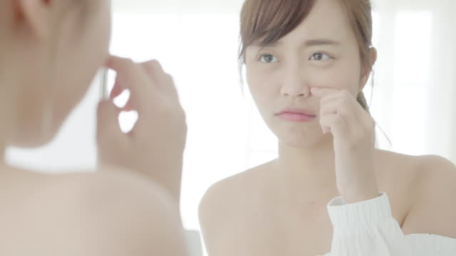 Beautiful portrait young asian woman looking the mirror and touch face is a acne, zit treatment, girl problem beauty and skin, perfect with wellness in the bedroom at home with skin care and health concept.
