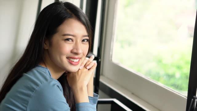 美しい肖像画若いアジアの女性がリビング ルーム、女の子で自信を持って笑顔と満足して窓際の椅子に座ってカメラ、ライフ スタイルのコンセプト、スローモーションを見て幸せとのさよ� - スーパーモデル点の映像素材/bロール