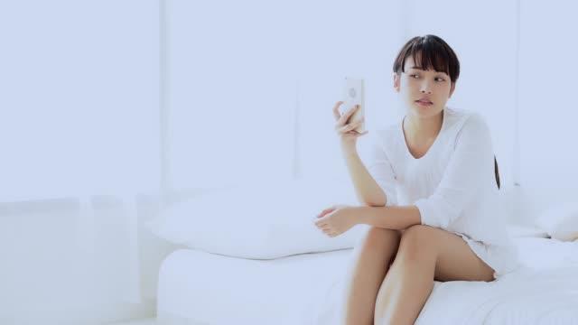 美しい肖像画若いですアジアの女性座っていますスマートな携帯電話でセルフを取ってベッドルーム上の寝室に自宅では、女の子は楽しい、ライフスタイルのコンセプトで笑顔で撮影してい� - 美人点の映像素材/bロール