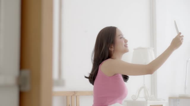 Beautiful portrait young asian woman sitting taking a selfie with smart mobile phone on bedroom in the morning at home, girl is photographing happy and smile with fun, lifestyle concept, slow motion.