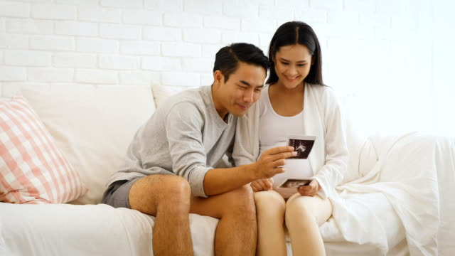 Belle femme enceinte et son mari tiennent échographie sur le ventre dans le canapé à la maison, enceintes et notion de famille - Vidéo