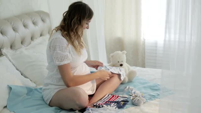 beautiful pregnant women in white dress looking at babies clothes. - abbigliamento da neonato video stock e b–roll