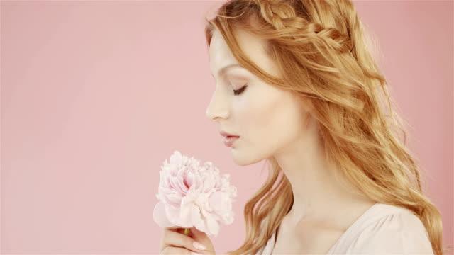 vacker söt flicka med magnifik rosa blomma. - femininitet bildbanksvideor och videomaterial från bakom kulisserna