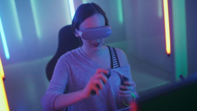 sanal gerçeklik kulaklık giyen güzel yanlısı bir oyun kız online video oyunda kullanarak denetleyicilerinin el hareketi çalış. cool retro neon odaya renkler. - sanal gerçeklik stok videoları ve detay görüntü çekimi