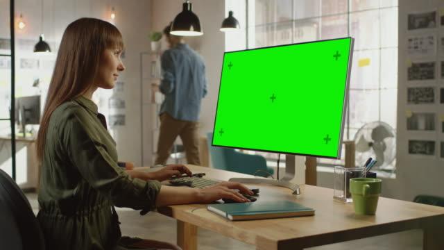 Schöne professionelle kreative Mitarbeiterarbeitet auf ihrem Personal Computer mit Big Green Screen Mock Up Display. Sie arbeitet in einem coolen Office Loft. Andere männliche Kollegen geht im Hintergrund. – Video