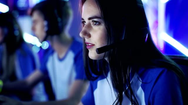 美しくプロのゲーマーの女の子、彼女チームが esport サイバーのゲーム大会に参加します。彼女は彼女のヘッドフォンを持っているし、チームのリーダーとして彼女はマイクに戦略的な操縦をコマンドします。 - ゲーム ヘッドフォン点の映像素材/bロール