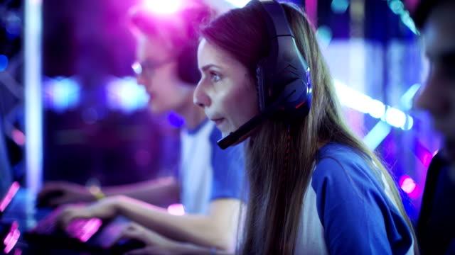 美しくプロのゲーマーの女の子、彼女チームが esport サイバーのゲーム大会に参加します。彼女は彼女のヘッドフォンと協議のマイクに向かって。 - ゲーム ヘッドフォン点の映像素材/bロール