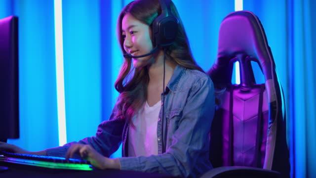 vídeos de stock e filmes b-roll de beautiful professional gamer girl sitting down to play online video game - só mulheres jovens