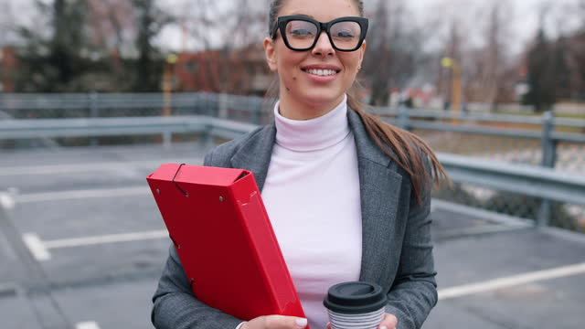Beautiful professional woman enters her white car in the public parking lot, holding documents and coffee in her hand video