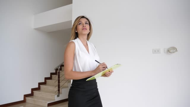 Beautiful real estate agent checking the property and writing down everything on a document on clipboard