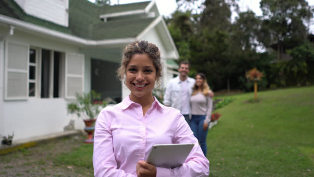 Beautiful real estate agent smiling at camera and couple customer at background video