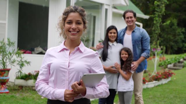 vackra mäklaren inför kameran leende hålla en tablett och familj i bakgrunden - fast egendom bildbanksvideor och videomaterial från bakom kulisserna