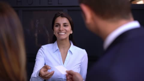 Beautiful receptionist at the hotel handing key to business couple checking in Beautiful friendly receptionist at the hotel handing key to business couple checking in service stock videos & royalty-free footage