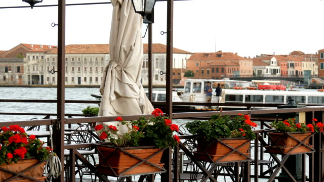 Beautiful red flowers in pots on a Grand Canal embankment in Venice in the background a boat passing through with tourists