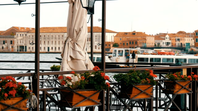 vídeos de stock e filmes b-roll de beautiful red flowers in pots on a grand canal embankment in venice in the background a boat passing through with tourists - lago maggiore