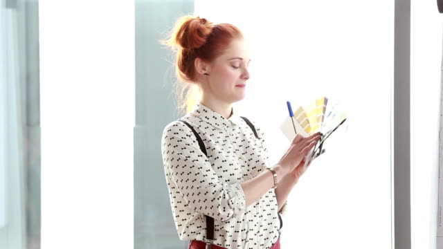 Beautiful red hair woman holding color fan deck during presentation video