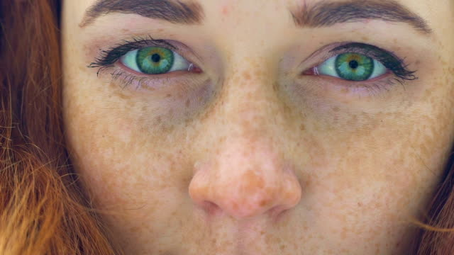 beautiful red haired girl with freckles and green eyes extreme close up, slow - zbliżenie filmów i materiałów b-roll