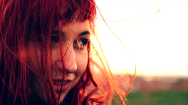 Beautiful red haired young woman enjoying windy spring day on hill upper the town video