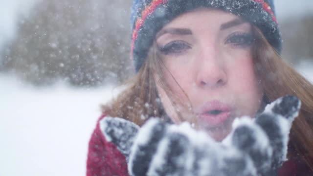 vídeos de stock, filmes e b-roll de bela jovem cabeça vermelha está soprando neve na câmera em super câmera lenta 120fps - soprando