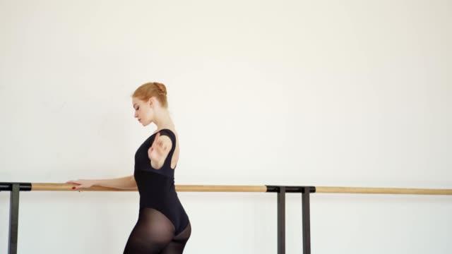 schöne rotschopf ballerina in schwarzem trikot üben port de bhs bei barre im ballettstudio, seitenansicht tracking schuss - gymnastikanzug stock-videos und b-roll-filmmaterial