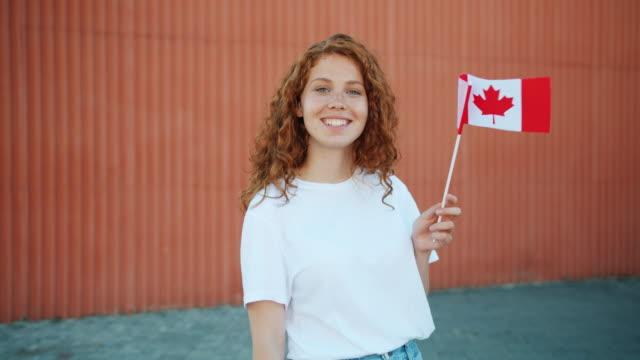 beautiful redhead teenager waving canadian flag outdoors looking at camera - canada flag stock videos & royalty-free footage