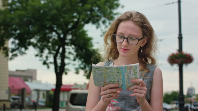 A Beautiful Redhead Tourist Using a Map Outdoors video