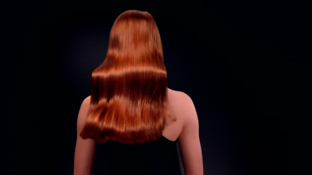 Beautiful redhead woman tossing her long hair Studio shot of attractive ginger woman tossing her healthy, long hair. Super slow motion. redhead stock videos & royalty-free footage