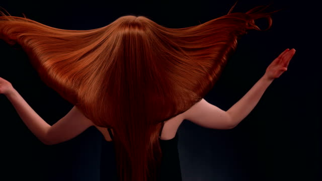 Beautiful redhead woman tossing long hair Studio shot of attractive redhead woman tossing her healthy, long hair. Super slow motion long hair stock videos & royalty-free footage